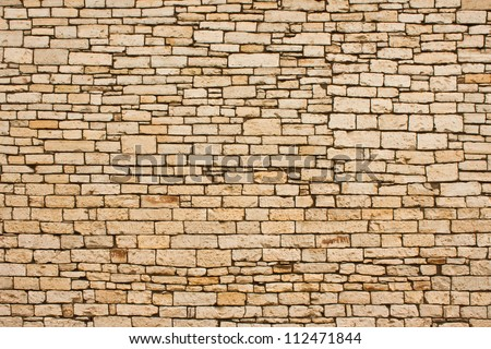 A large section of hand-cut stone wall on an historic building exterior. - stock photo