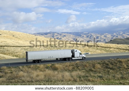 A large semi trailer rig hauls a load from California eastward into the Sierra Nevada Mountains - stock photo