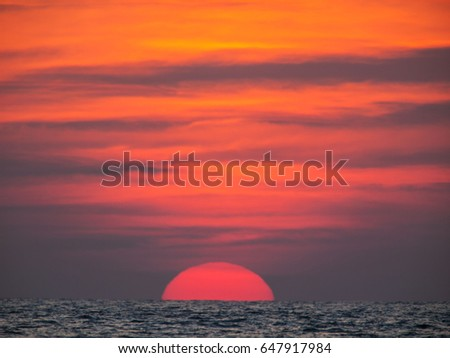 A large setting sun under an orange sky sits at the bottom of the frame about to disappear behind the horizon. Taken at Ko Kut island in east Thailand