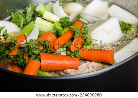 A large stock pot on a stove with vegetables cut for making soup - stock photo