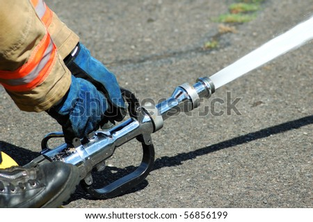 A large straight steam nozzle attached to a 3 inch hose for exposure protection at a structure fire. - stock photo