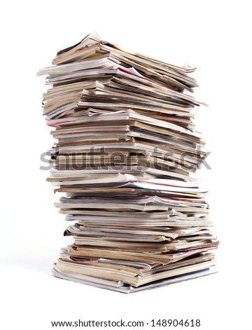 A large tall stack of magazines against a white background.
