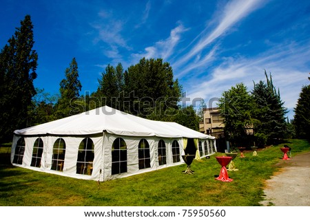 A large tent outside under a cloudy blue sky
