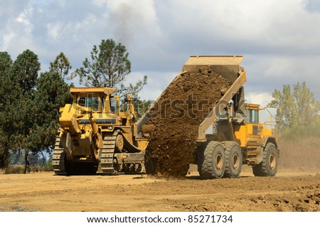 A large track bulldozer and a large articulating dump truck at a new road project in Oregon
