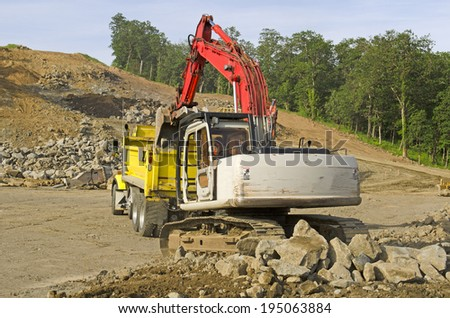 A large track hoe excavator loads a dump truck with dirt and rock on a new commercial construction development