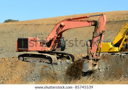 A large tracked excavator working a rock pile for a new interstate 5 interchange near Roseburg Oregon