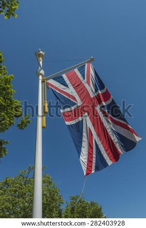A large union flag flying from an ornate flagpole in the summer breeze