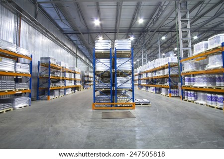A large warehouse. Pallet metal racks with a heavy load.