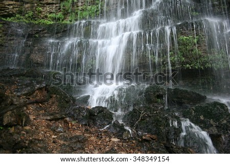 A large waterfall cascading over a mossy stone cliff - stock photo