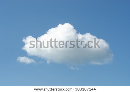 A large white fluffy cloud floating in a blue sky. - stock photo