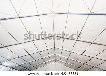 A large white tent in a grass field for parties and entertaining - stock photo
