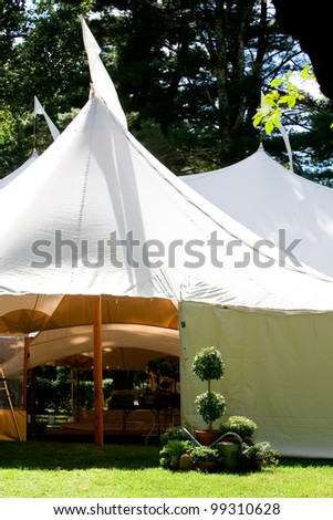 a large white wedding tent set up outside for a catered event - stock photo