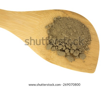 A large wood spoon with a portion of comfrey root powder on a white background. - stock photo