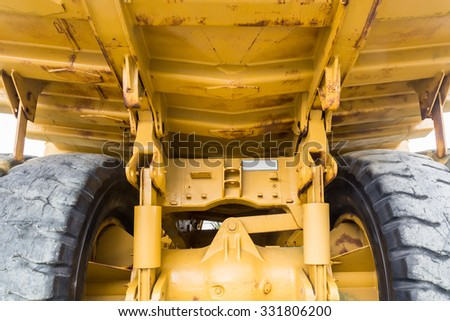 A large yellow truck seen from below and behind at low angle