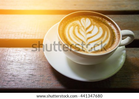 A Latte Coffee cup art on wooden desk. - stock photo