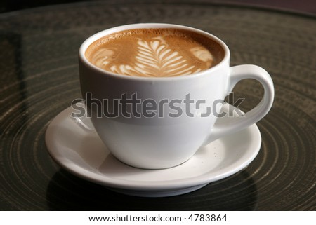 "a latte with ""latte art"" in foam in a ceramic cup in seattles world famous pike place market aka farmers market - stock photo"
