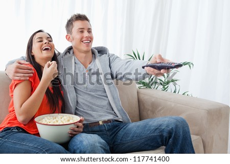 A laughing couple with popcorn as they change the tv with a remote and sit on the couch