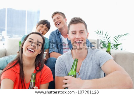 A laughing group inside the house enjoying beer and having fun together - stock photo