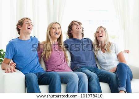 A laughing group of fiends as they sit on the couch together