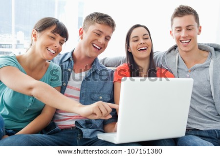 A laughing group of friends around a laptop watching the screen as they sit with one girl pointing the screen - stock photo