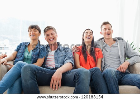 A laughing group of friends look ahead into the camera while on the couch