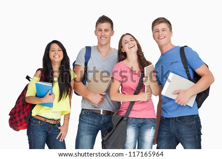 A laughing group of students with notepads and backpacks as they look at the camera - stock photo