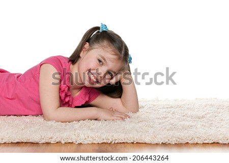 A laughing little girl is lying on the white carpet - stock photo