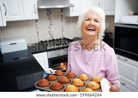 A laughing pensioner holding a tray of baked muffins just out of the oven - stock photo