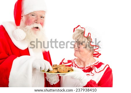 A laughing Santa takes a cookie from the plate Mrs Clause offers him. - stock photo