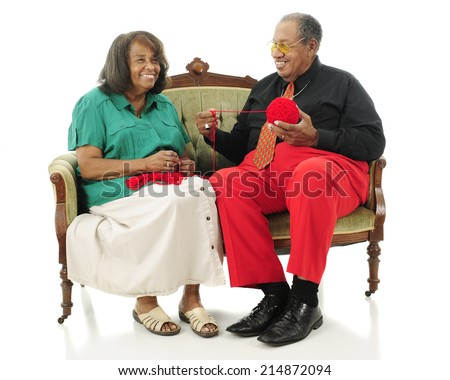 A laughing senior couple sitting on a sofa while she starts a crochet project.  They're wearing Christmas colors.  Isolated on white - stock photo