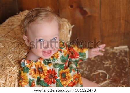 A laughing, six month old, baby girl wearing a floral romper in fall colors. She is sitting and leaning against a small straw bale. Shot in the studio on a wood paneled floor and background.