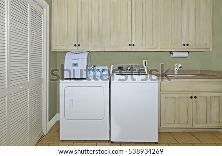 A Laundry Room With Washer,dryer,ice Maker,sink,cabinets,and