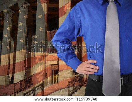 A law man is standing against a government building and American flag in the background. Add your message to the copyspace. - stock photo