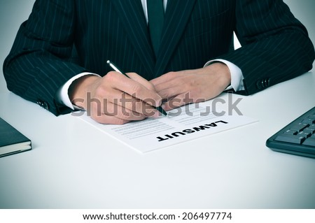 a lawyer in his office with a document with the text lawsuit written in it - stock photo