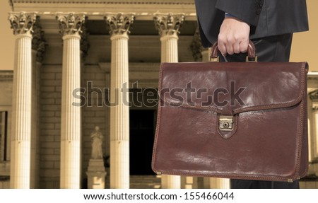 A lawyer with a briefcase on the background of the courthouse - stock photo