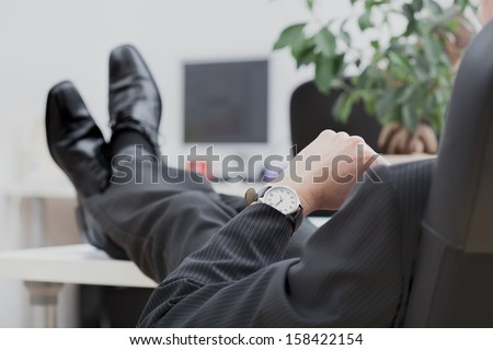 A lazy businessman sitting disrespectfully with his legs on the desk