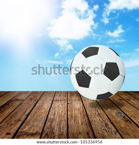 A Leather black and white ball on wooden floor and blue sky