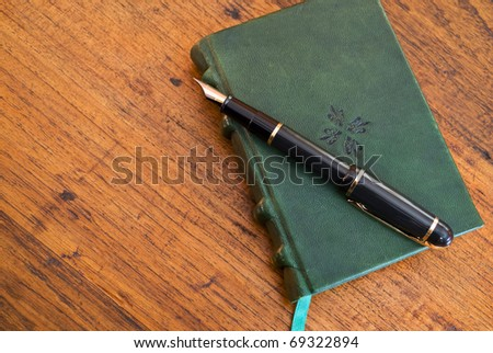 A leather-bound journal with pen lying on wooden desk, copy space at left
