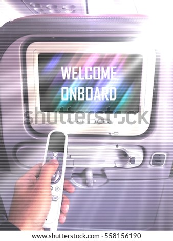 "A left hand holding remote control facing screen monitor behind seat with text ""Welcome Onboard"". Special effect tone with sun light and ray of lights through from the window."