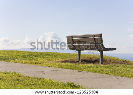 A leisurely stroll. A paved pathway runs along the top of a green grassy cliff in a suburban park. A wooden bench top faces a blue sky and clouds, offering a relaxing place to rest after a long walk. - stock photo