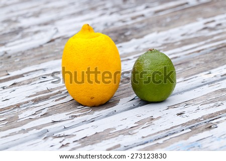 a lemon and a lime on wooden table with flaking paint slightly from above - stock photo