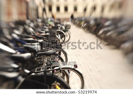 A lens blurred photo of lots of parked bikes. Symbolic content. - stock photo