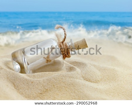 A letter in a bottle on the beach - stock photo