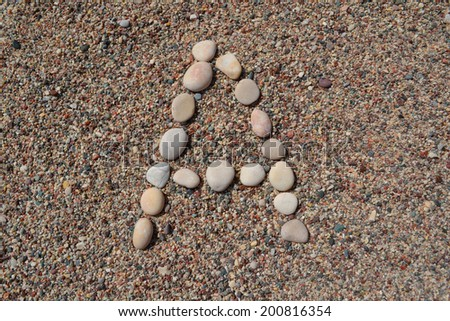 A letter made of stones on sand - stock photo