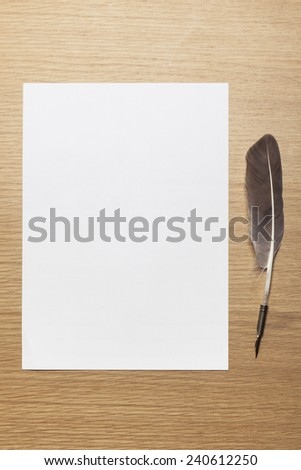 a letter paper and feather quill pen on the wood desktable top