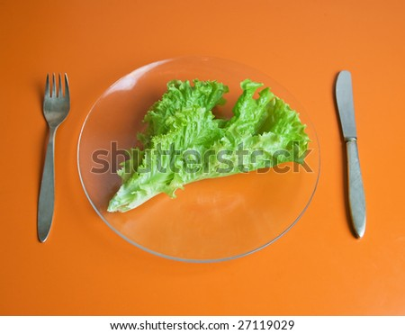 A lettuce leaf on a glass plate, fork and knife