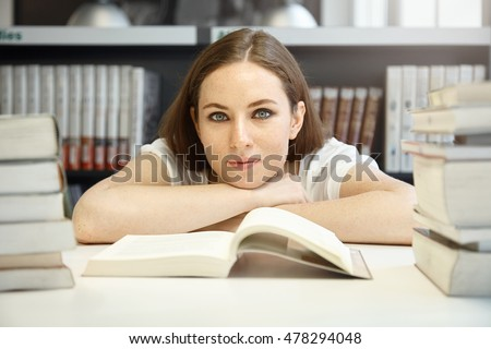 A-level student girl with freckles looking happy and calm, sitting in front of open textbook on Geography, studying foreign countries and nationalities. Young Caucasian woman reading at library