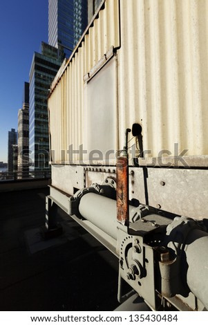 A Level that controls the gouge installed between the metal pipes, part of an outdoor industrial HVAC air-conditioner system. In the background - midtown Manhattan skyscrapers. - stock photo