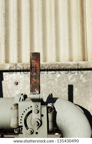 A Level that controls the gouge installed between the metal pipes, part of an outdoor industrial HVAC air-conditioner system. - stock photo