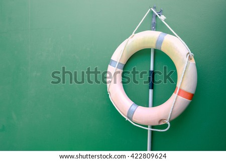 A life buoy on green cement wall - stock photo